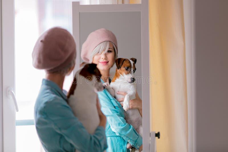 Mädchen mit Hund nahe einem Spiegel stockfotos