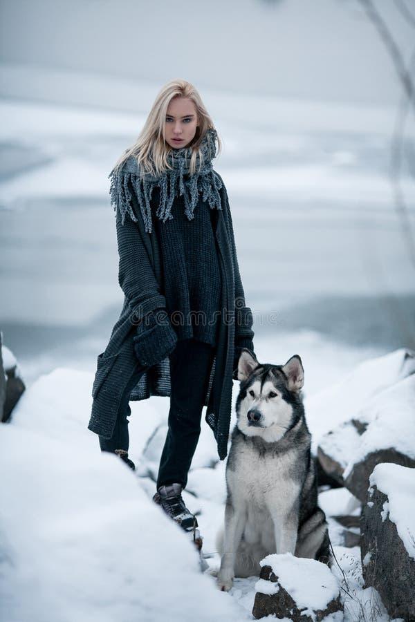 Mädchen mit Hundmalamute unter Felsen im Winter stockfotografie