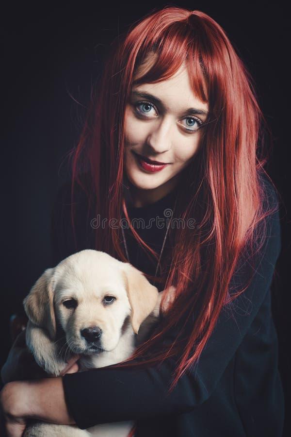 Mädchen mit ihrem Labrador Retriever Hund auf schwarzem Grund lizenzfreies stockfoto