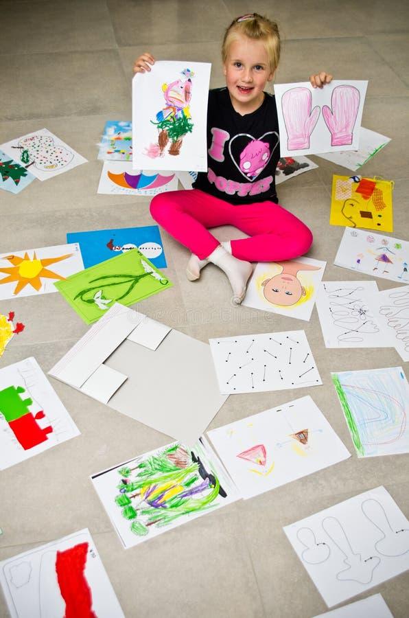 Mädchen mit ihren Zeichnungen auf dem Boden stockbild