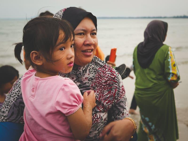 Mädchen mit ihrer Mutter, die wartet, um die Babyschildkröte dem Meer freizugeben stockfotos