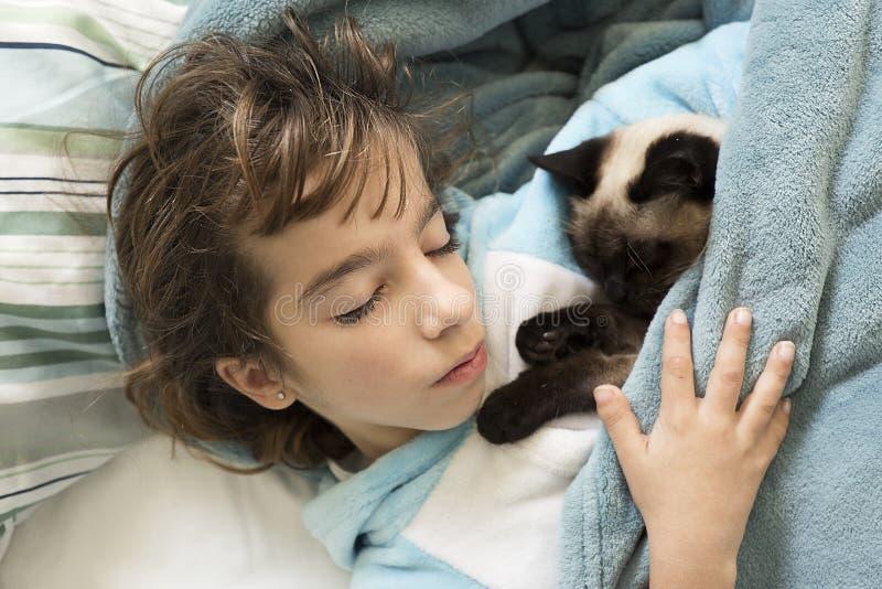 Mädchen mit 10-Jährigen, das im Bett mit ihrer Katze auf die Oberseite schläft stockfotografie
