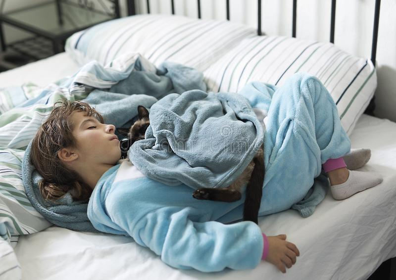 Mädchen mit 10-Jährigen, das im Bett mit ihrer Katze auf die Oberseite schläft lizenzfreie stockbilder