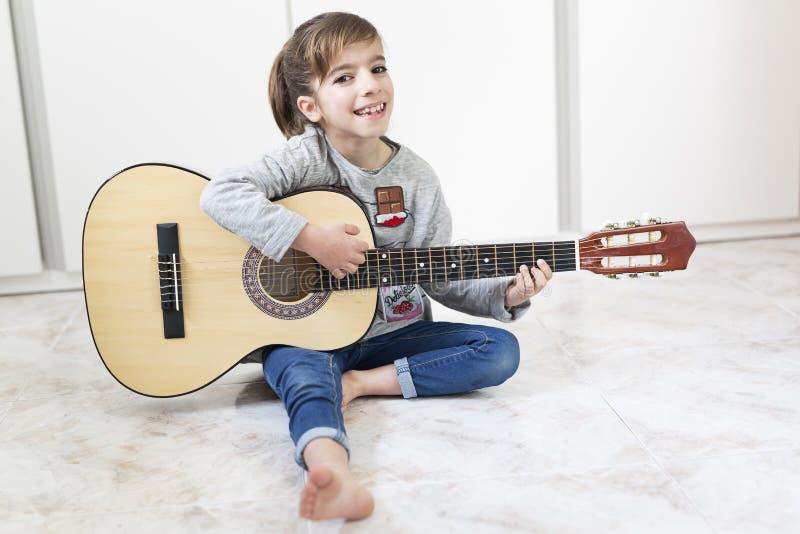 Mädchen mit 9-Jährigen, das lernt, die Gitarre zu spielen lizenzfreie stockfotos