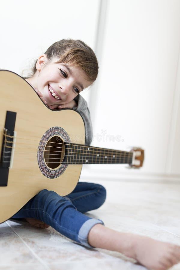 Mädchen mit 9-Jährigen, das lernt, die Gitarre zu spielen lizenzfreie stockbilder