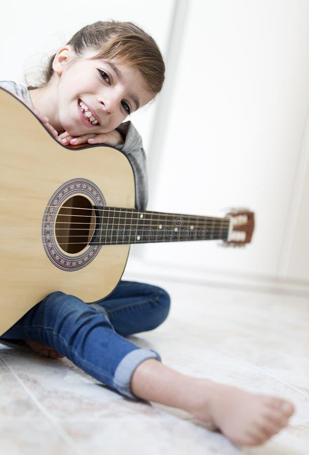 Mädchen mit 9-Jährigen, das lernt, die Gitarre zu spielen lizenzfreie stockfotografie