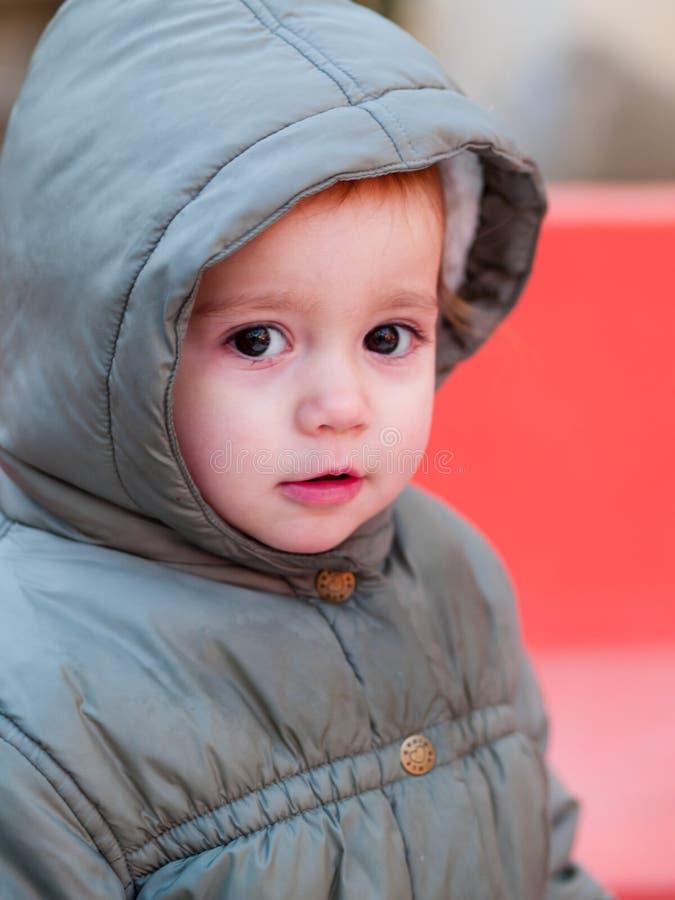Mädchen mit 2-Jährigen mit einer Haube ihrer Jacke lizenzfreies stockfoto