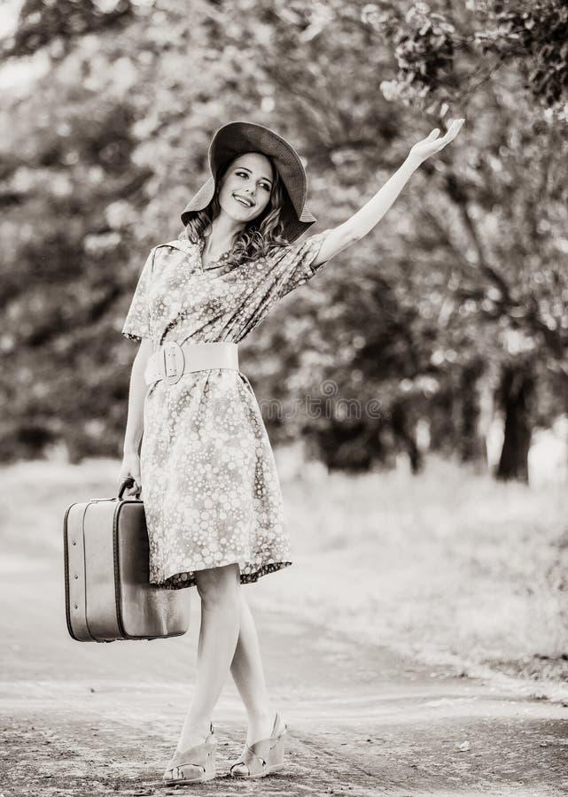 Mädchen mit Koffer an der Gasse des Baums stockbilder