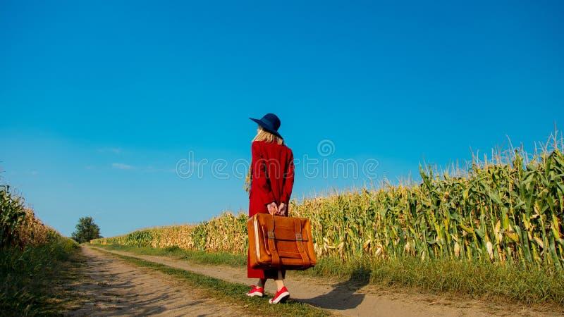 Mädchen mit Koffer nahe Getreidefeld stockfotos