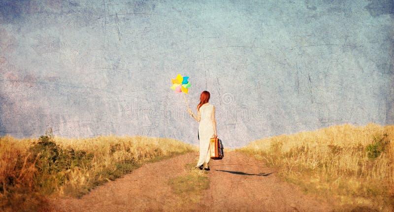 Mädchen mit Koffer und Wind spielen an der Landschaft stockfotografie