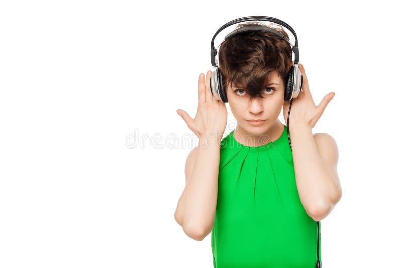 Mädchen mit Kopfhörern in einem grünen Hemd auf einem Weiß lizenzfreies stockbild