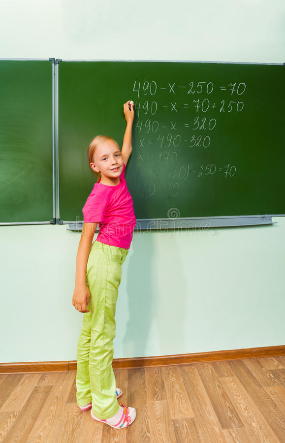 Mädchen mit Kreide in der Hand Gleichung schreibend lizenzfreie stockfotografie
