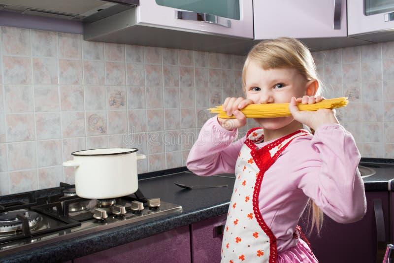 Mädchen mit Makkaroni in der Küche lizenzfreie stockfotografie