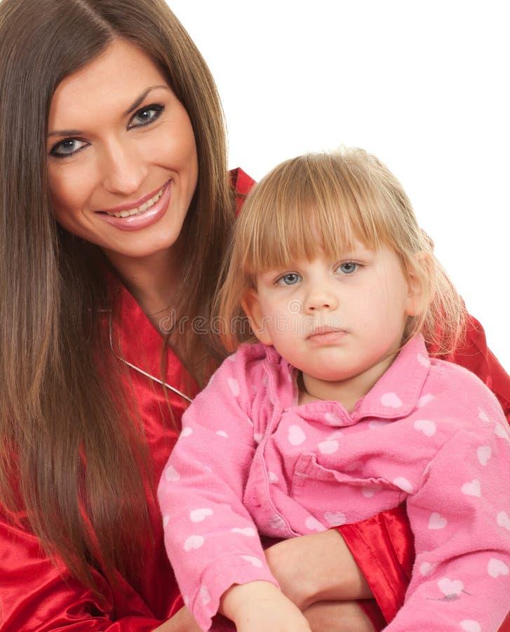 Mädchen mit Mutter in der weißen Bettwäsche stockfotos