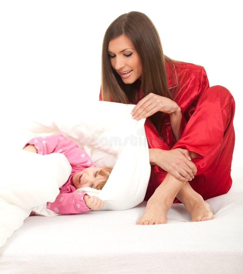 Mädchen mit Mutter in der weißen Bettwäsche stockbild