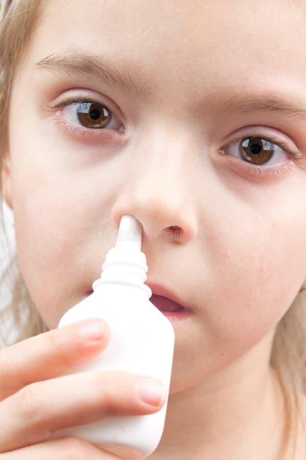 Mädchen mit Nasenspray stockbilder
