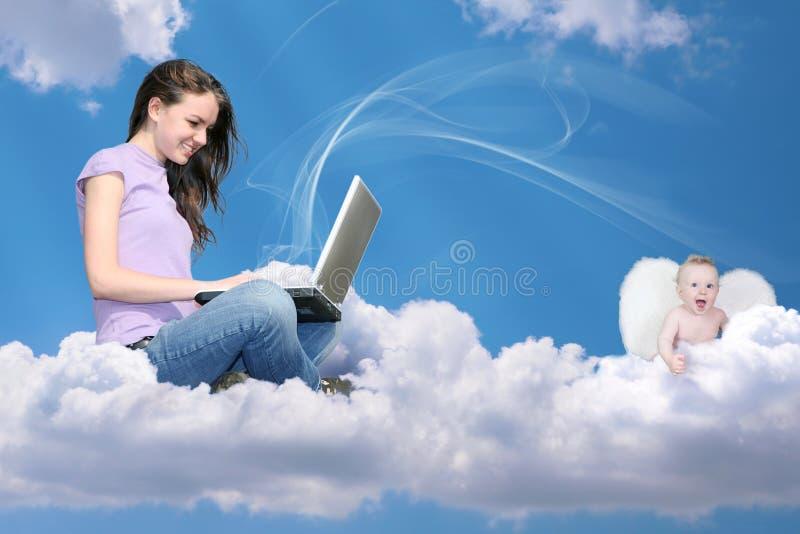 Mädchen mit Notizbuch auf Wolke und wenigem Engel stockfoto