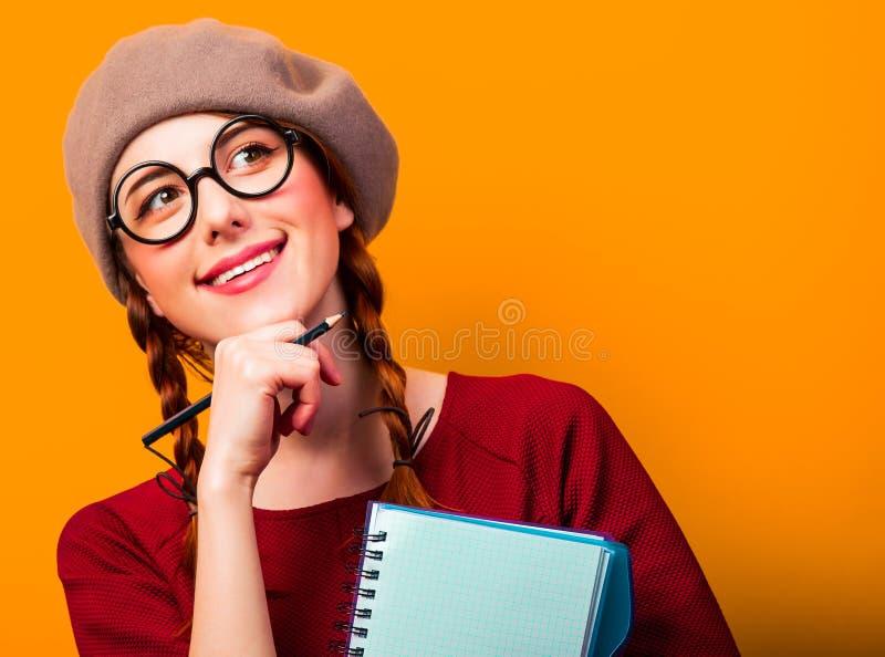 Mädchen mit Notizbuch und Bleistift auf gelbem Hintergrund lizenzfreie stockfotos