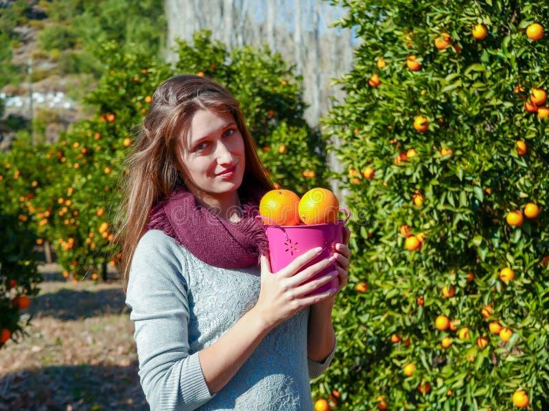 Mädchen mit Orangen im Garten lizenzfreie stockfotos