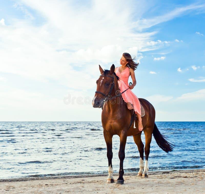 Mädchen mit Pferd auf Seeküste lizenzfreie stockbilder