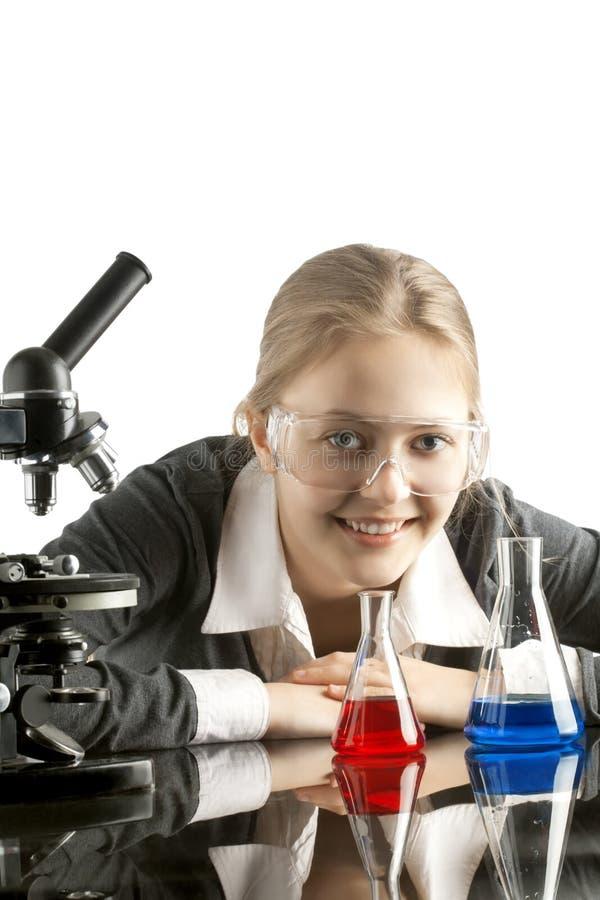 Mädchen mit Reagenzgläsern und Mikroskop für chemische Klasse stockbilder
