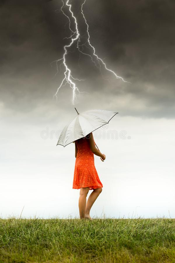 Mädchen mit Regenschirm im Sturm lizenzfreie stockfotos