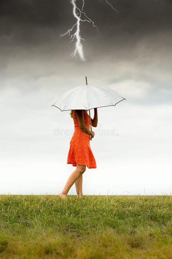 Mädchen mit Regenschirm im Sturm lizenzfreie stockbilder