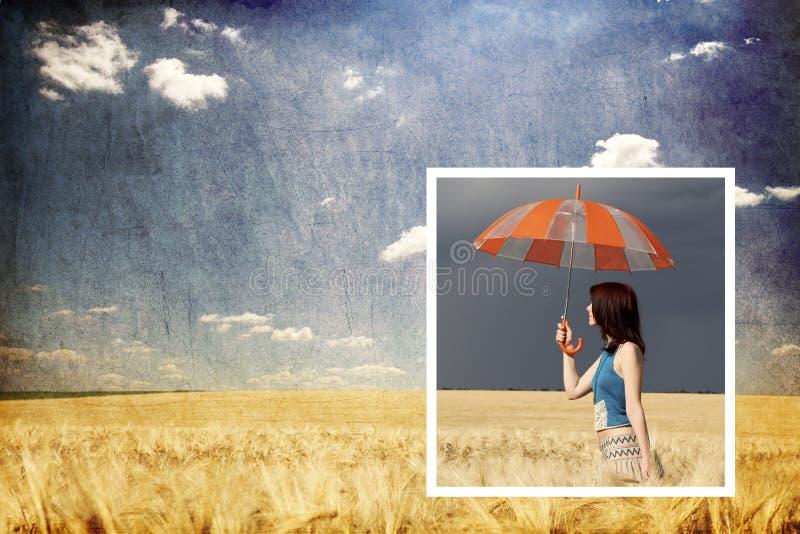 Mädchen mit Regenschirm im Sturm am Weizenfeld stockfoto