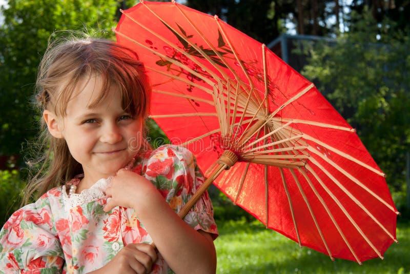 Mädchen mit rotem Regenschirm stockbild