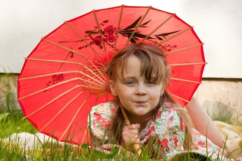 Mädchen mit rotem Regenschirm stockfotografie