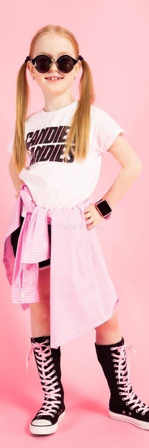 Mädchen mit roten Endstücken auf einem rosa Hintergrund Ein reizend Mädchen in der heller Sportkleidung und -Sonnenbrille setzte  stockfotos