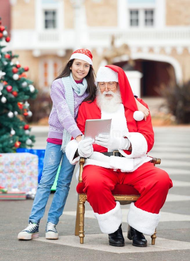 Mädchen mit Santa Claus Using Digital Tablet lizenzfreie stockfotografie