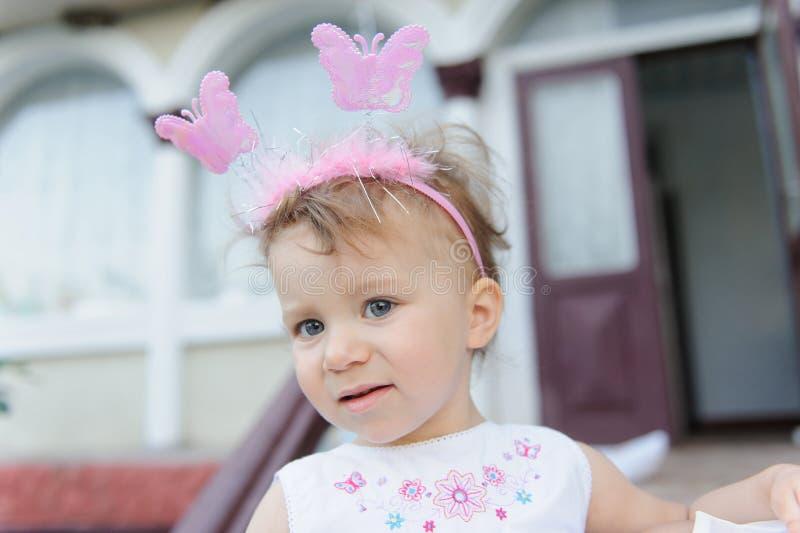Mädchen mit Schmetterlingen auf Stirnband stockbilder