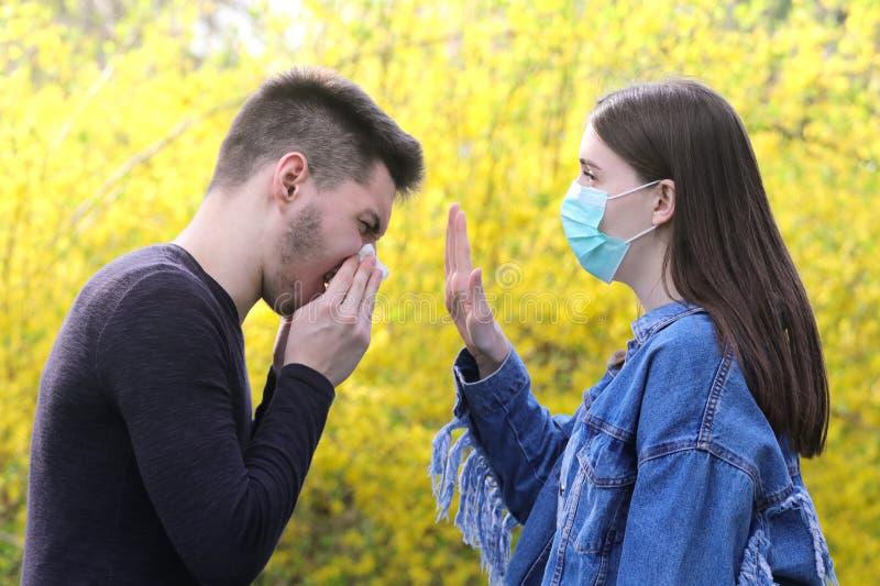 Mädchen mit Schutzmaske und kranker niesender Junge, stoppen die Grippe e lizenzfreies stockfoto
