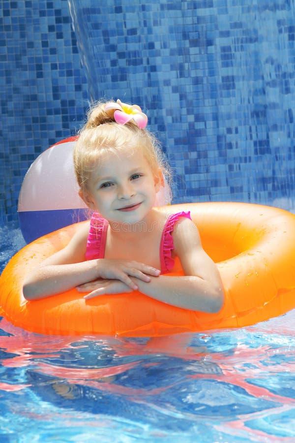 Mädchen mit Schwimmenkreis im Pool lizenzfreie stockfotografie