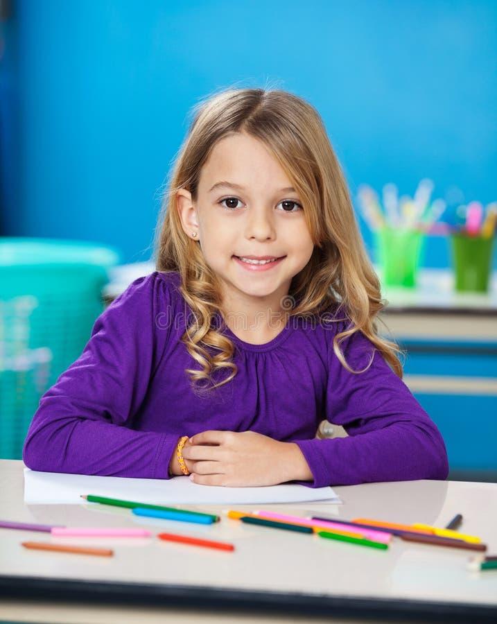 Mädchen mit Skizzen-Stiften und Papier im Kindergarten lizenzfreie stockfotos