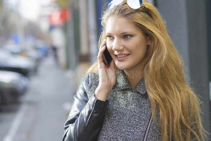 Mädchen mit Smartphone gehend auf Stadt lizenzfreie stockbilder