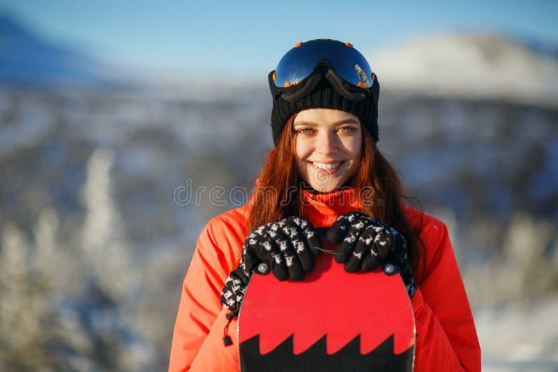 Mädchen mit Snowboard auf dem Berggipfel stockfoto