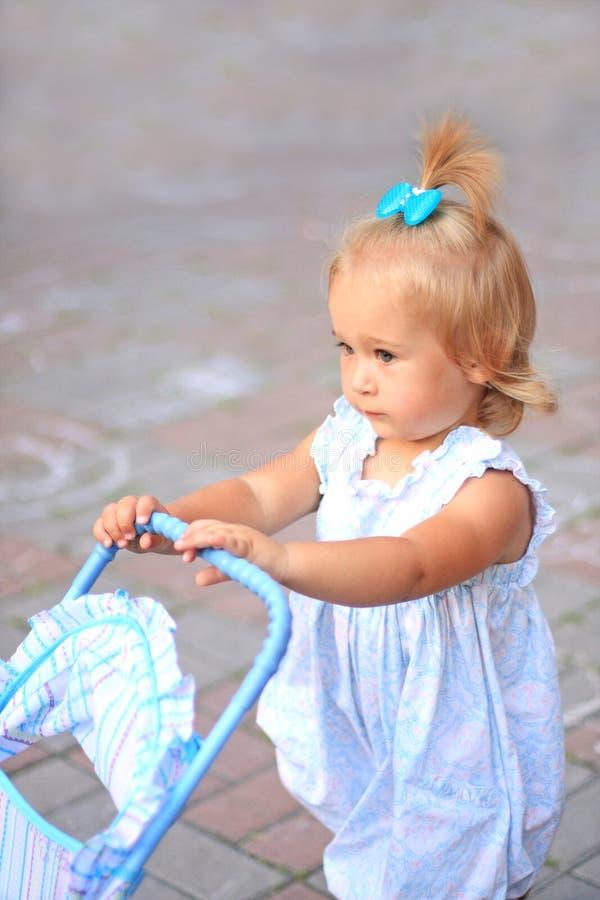 Mädchen mit Spielzeug Pram stockbilder