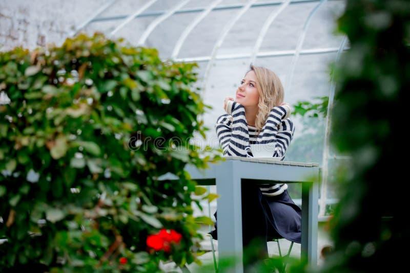 Mädchen mit Tasse Kaffee im Herbstsaisongarten lizenzfreie stockfotografie