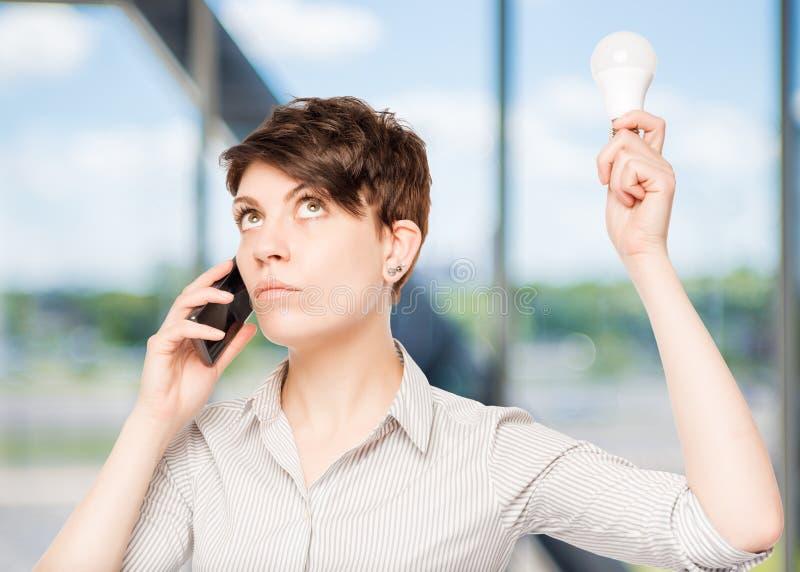 Mädchen mit Telefon und Lampe in der Handaufstellung lizenzfreie stockfotografie