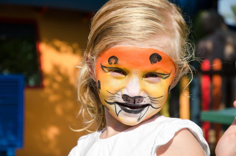 Mädchen mit Tigergesichtsmalerei stockfoto