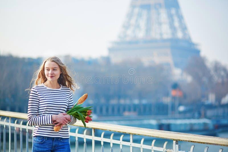 Mädchen mit traditionellem französischem Stangenbrot und Tulpen lizenzfreie stockfotografie
