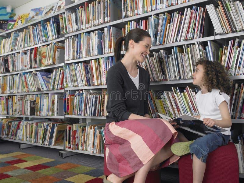 Mädchen mit unterrichtendem Lesegeschichten-Buch in der Bibliothek lizenzfreie stockfotos