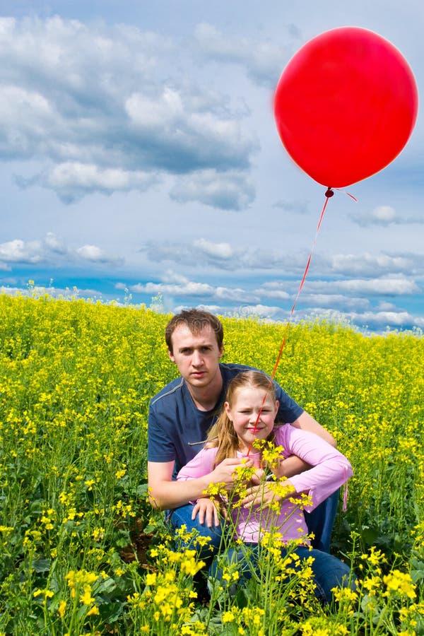 Mädchen mit Vater und rotem Ballon in der Wiese lizenzfreies stockbild