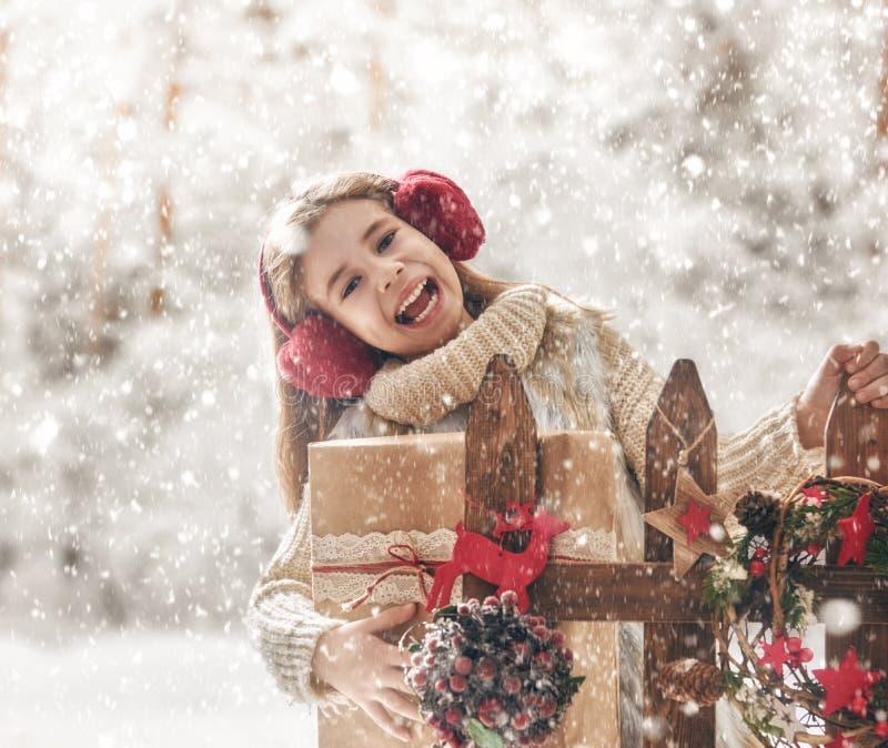 Mädchen mit Weihnachtsgeschenk auf einem Winterweg lizenzfreie stockfotos