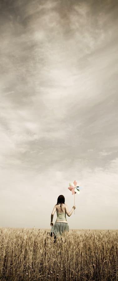 Mädchen mit Windturbine am Weizenfeld. Foto in v lizenzfreie stockbilder