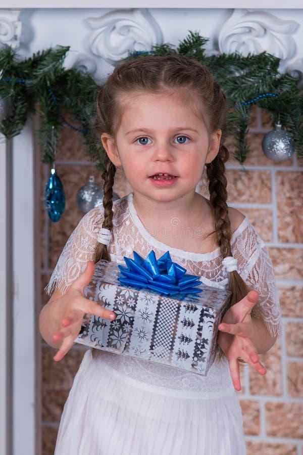 Mädchen mit zwei Zöpfen mit einem Geschenk in einem Kasten im Feiertag der neuen Jahre lizenzfreies stockfoto