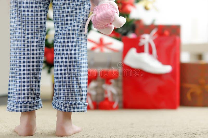 Mädchen morgens, das nach Weihnachtsgeschenken sucht stockbild