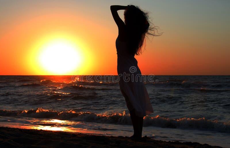 Mädchen nahe dem Meer auf Sonnenaufgang lizenzfreie stockfotos